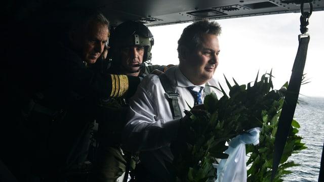 Minister mit Kranz im Helikopter