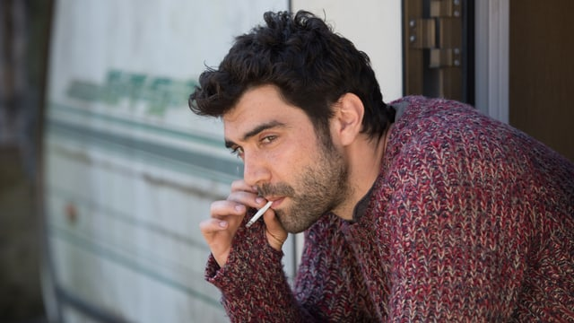 Ein junger Mann raucht.