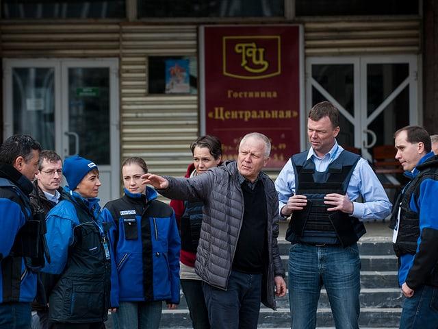 Ein Zivilist spricht mit einer Gruppe Personen in blauen OSZE-Uniformen.