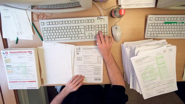 Ein Mann tippt auf dem Steueramt Zahlen einer Steuererklärung in den Computer