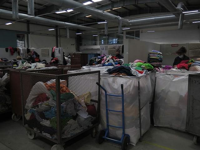 Frauen stehen in einer Halle vor grossen Kleidersäcken und sortieren die Teile.