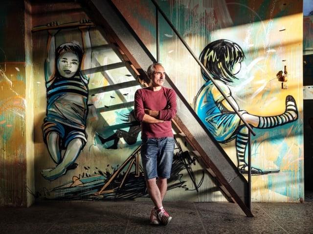 MAAM-Gründer Giorgio de Finis lehnt gegen eine Wand, auf die zwei Mädchen gesprayt sind.