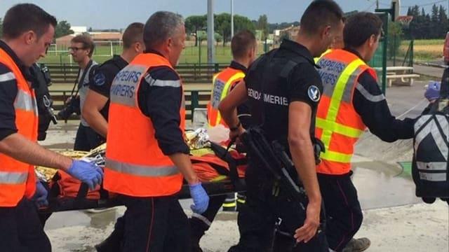 Rettungskräfte tragen einen Verletzten auf einer Trage weg.