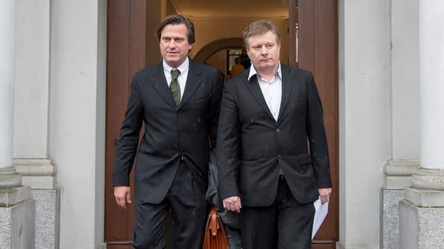 Zwei Männer verlassen ein Gebäude