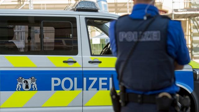 Polizeiauto der Basler Polizei, davor unscharf ein Polizist