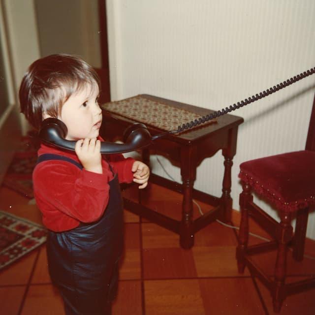 Ein kleiner Bub mit rotem Pullover und blauer Latzhose hält sich einen grossen schwarzen Telefonhörer ans Ohr.
