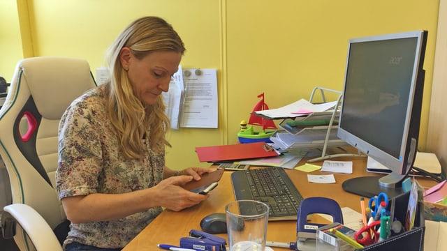 Claudia Rabelbauer sitzt am Schreibtisch und blickt in ihr Smartphohne