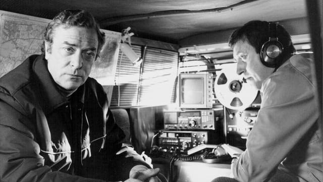 Zwei Männer sitzen in einem Abhör-Wagen