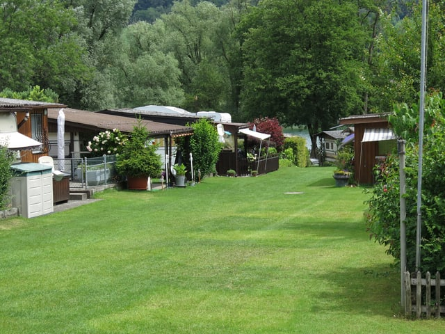 Rasenfläche mit Wohnwagen rundherum.