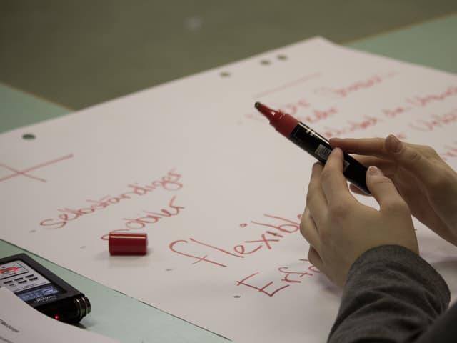 Eine Schülerin schreibt auf ein Papier.