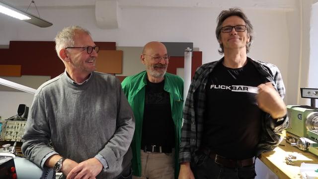 """Drei Männer, einer trägt ein T-Shirt mit der Aufschrift """"Flickbar"""""""