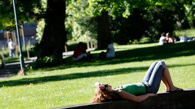 Eine Frau liegt im Platzspitzpark in der Sonne