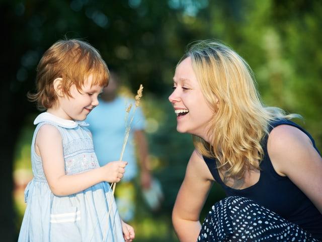 Lachendes Kind mit der Mutter draussen.