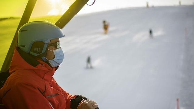 Skifahrer mit Gesichtsmaske auf einem Sessellift.