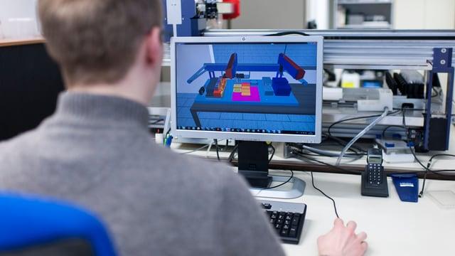 Aufnahme von hinten: Mann sitzt an Computer auf Bildschirm komplexe technische Zeichnungen