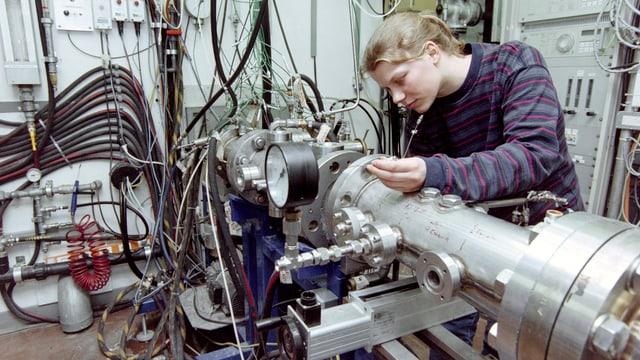 Eine junge Frau arbeitet an einer Maschine mit vielen Leitungen und Schläuchen.