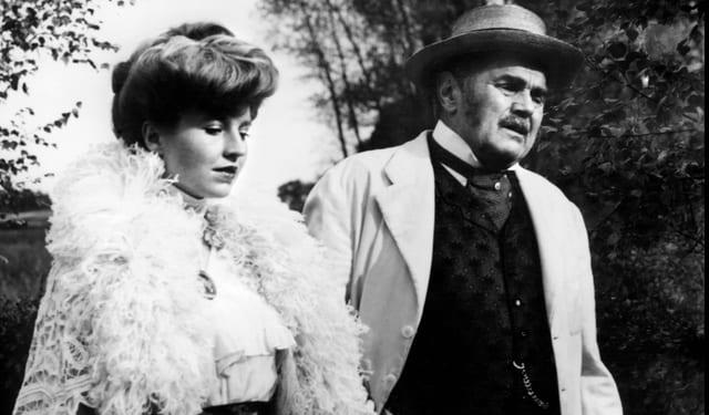 S/W-Blid: Mann und Frau in Kostümen, die das 19. Jahrhundert wiederspiegeln sollten, spazieren nebeneinander her.