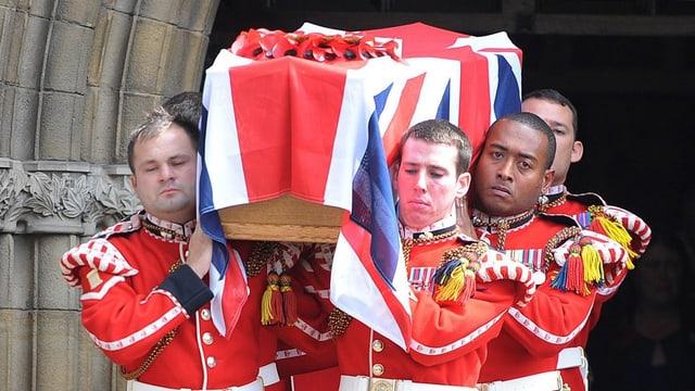 Kameraden in Uniform tragen Rigbys Sarg aus einer Kirche