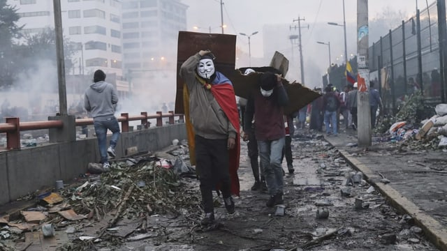 Maskierte Protestierende in den Strassen von Quito.