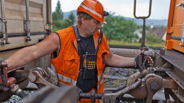 Ein Bahnangestellter hängt zwei Güterbahnwagen zusammen.