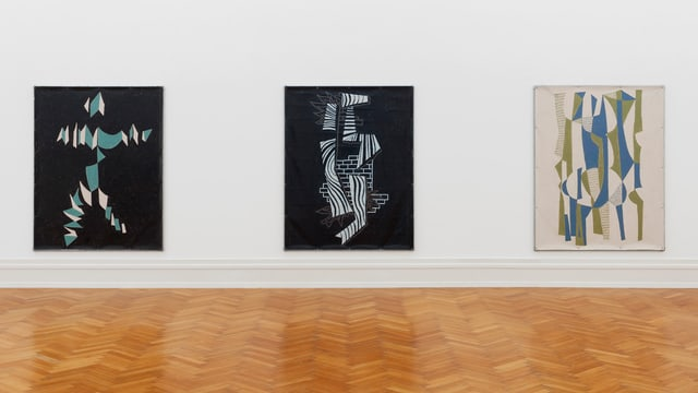 Drei abstrakte Bilder an einer Museumswand.