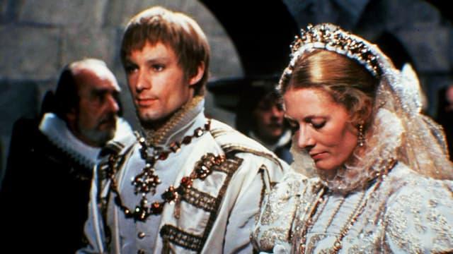 Eine Szene aus einem Film: Eine Frau und ein Mann stehen nebeneinander und haben die Hände zusammengelegt wie zum Gebet. Sie sind prunkvoll gekleidet, mit Krone, Ketten etc.