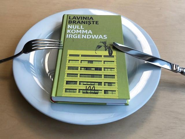 Lavinia Braniște Roman «Null Komma Irgendwas» liegt auf einem weissen Teller. Messer und Gabel daran angestellt.