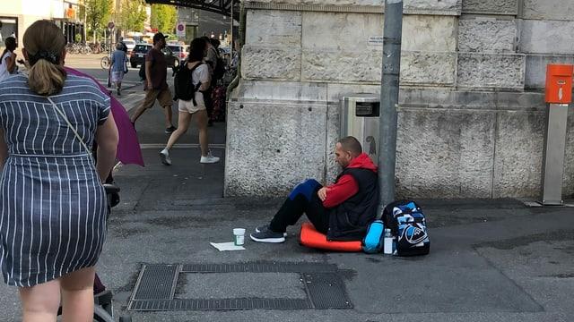 Ein Mann sitzt am Boden und bettelt um Geld.