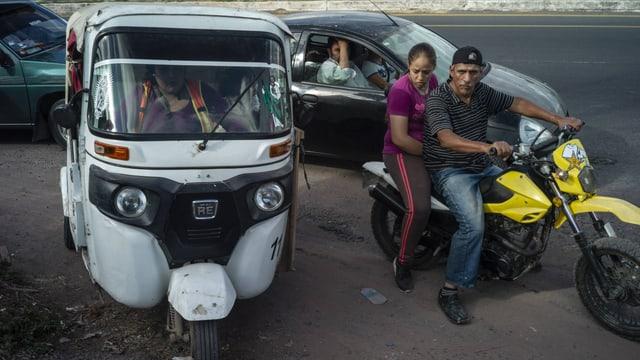 Dreirädriger Kleintransporter und zwei Personen auf einem Motorrad