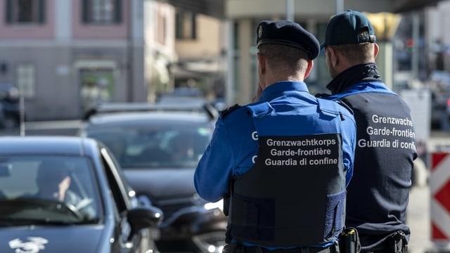 Dus emploiads da la guardia da cunfin observan ils autos che passan la duana.