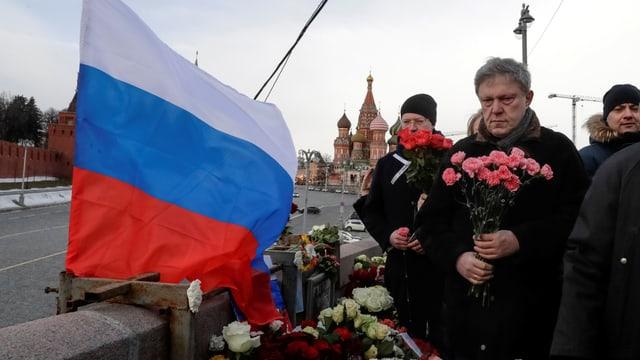 Mann mit Blumen und russischer Flagge.