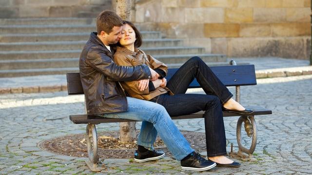 Ein junges Paar sitzt eng umschlungen auf einer Bank.