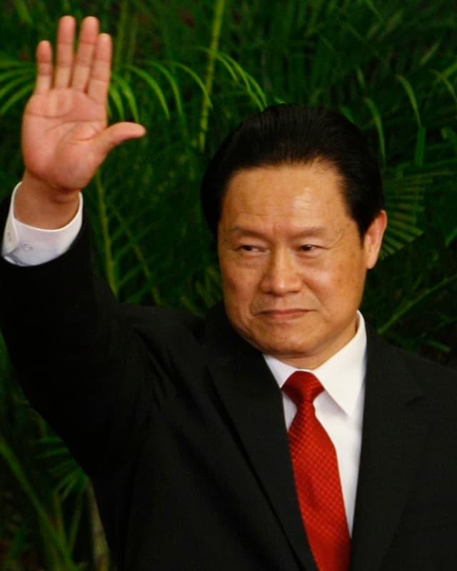 Ex-Sicherheitschef Zhou Yongkang winkt mit der rechten Hand. Er trägt einen Anzug mit roter Krawatte.