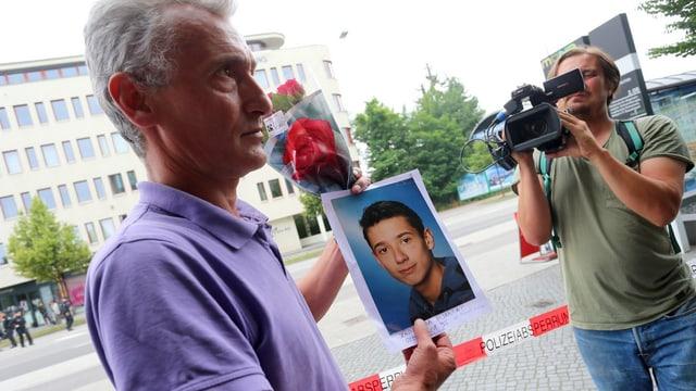 Ein Vater zeigt ein Bild seines getöteten Sohns.