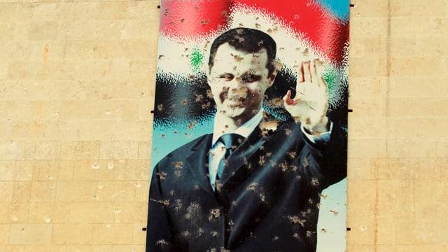 Ein zerschossenes Wandbild des syrischen Präsidenten Bashar al-Assad.