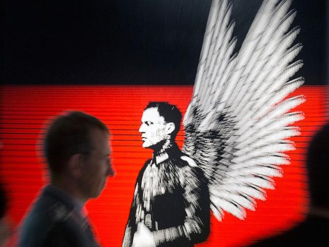 Eine Schwarz-weiss-Figur mit Engelsflügeln auf rotem Grund.