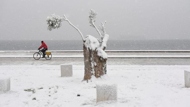 Mann auf Fahrrad auf schneebedeckter Strasse. Im HIntergrund das Meer.