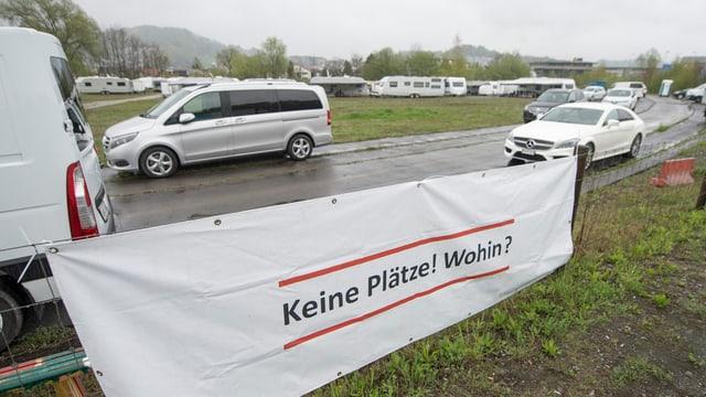 """Transparent mit der Aufschrift """"Keine Plätze! Wohin?"""" im Hintergrund Autos und Wohnwagen"""