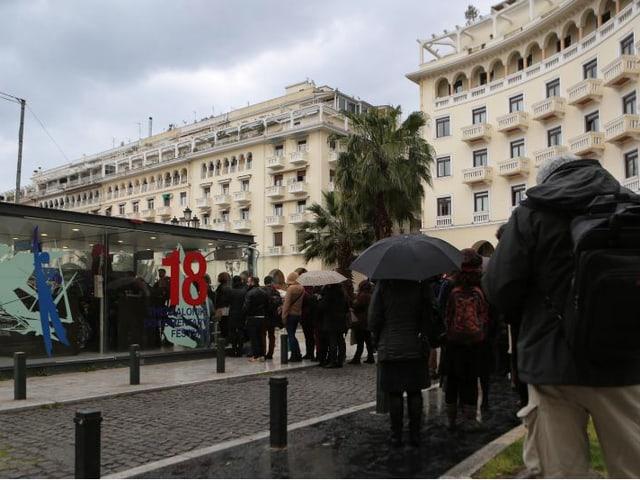 Blick auf einen Platz in Thessalonik. Menschen stehen vor einem Tickethäuschen an.