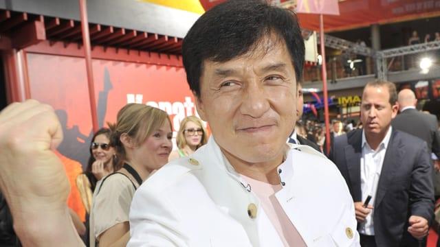 Jackie Chan streckt die Faust in die Kamera.