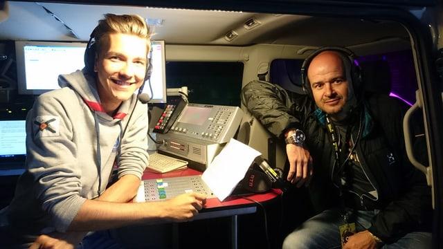 Norbert Cavegn (dre.) en il bus da RTR ensemen cun moderatur Livio Chistell.