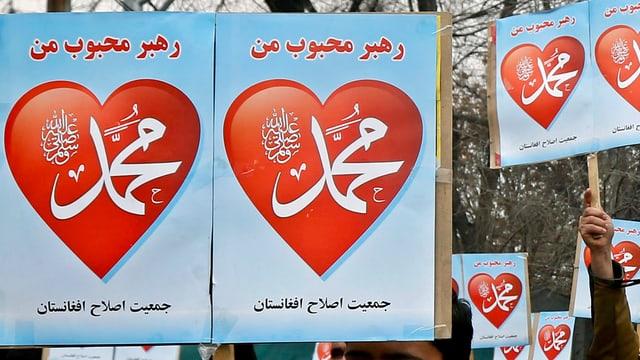 Blaue Schilder mit roten Herzen darauf. Darin arabische Schriftzeichen.