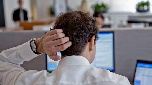 Ein Mann vor seinem Computer in einem Büro.