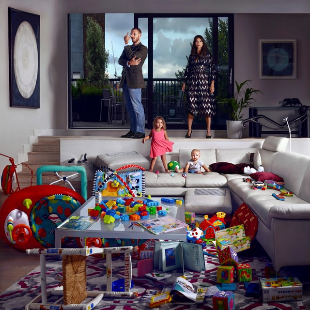 In einem Wohnzimmer türmen sich Kinderspielzeuge. Auf dem Sofa zwei kleine Kinder. Auf einer Ebene darüber stehen ein Mann und eine Frau.