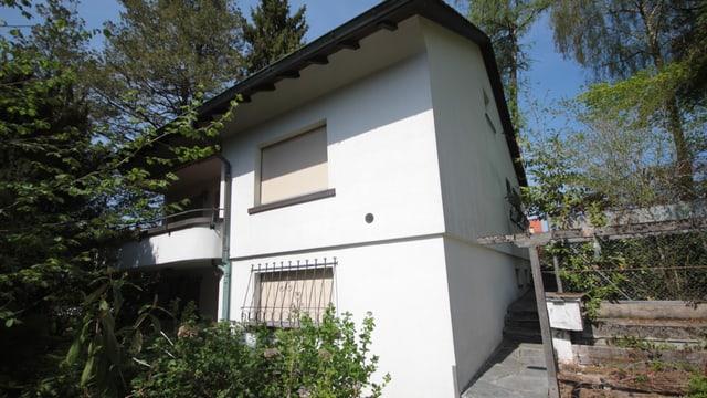 Ein älteres weisses Haus mit einem Balkon von hohen Bäumen umgeben.