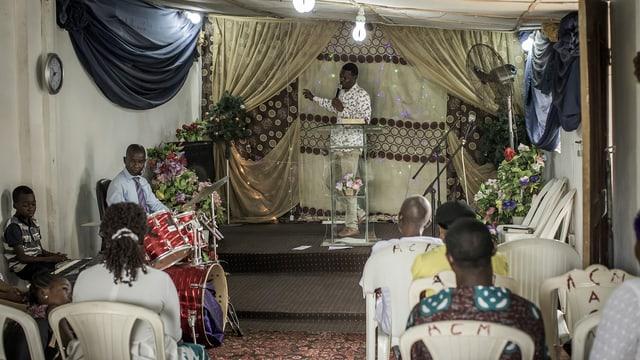 Ein Pastor vor wenigen Anhängern in einem kleinen Raum.