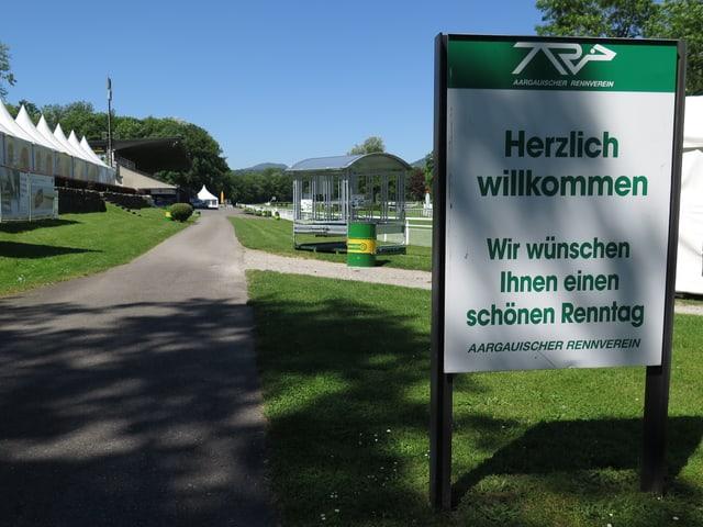 """Blick auf die Rennbahn, davor ein Schild mit der Aufschrift: """"Herzlich willkommen""""."""