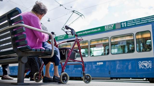 Frau auf einer Bank mit Rollator, vor ihr fährt ein blaues Tram vorbei.