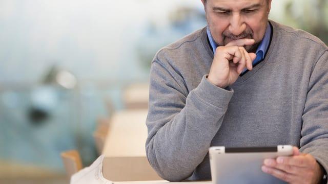 Ein Mann schaut mit nachdenklichem Blick auf ein iPad
