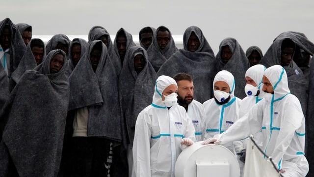 Flüchtlinge in dunkelgraue Wolldecken gehüllt stehen im Hintergrund. Im Vordergrund Helfer in weissen Schutzanzügen mit Mundschutz.